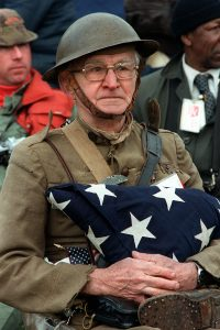 oseph Ambrose, an 86-year-old World War I veteran, attends the dedication day parade for the Vietnam Veterans Memorial in 1982. He is holding the flag that covered the casket of his son, who was killed in the Korean War. Photo: Department of Defense.